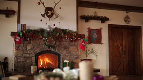 Fire burn in a fireplace decorated with garland lights, wreath, stockings and gift boxes on Christmas eve. New Year. Holidays celebration. Dolly shot,1080p Full stock footage