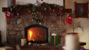 Fire burn in a fireplace decorated with garland lights, wreath, stockings and gift boxes on Christmas eve. New Year. Holidays celebration. Dolly shot,1080p Full stock video footage