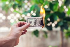 Fire burn one hundred dollars in hand royalty free stock photo