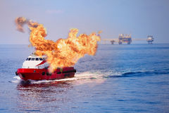 Fire burning on the boat in offshore oil and gas industry, emergency case and firefighter working for protection boat and working. Area Stock Image