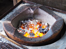 Fire burning charcoal in traditional clay stove Stock Image