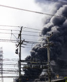 Fire burning factory near electricity post Stock Photos