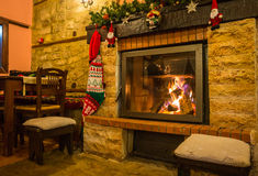 Fire burning in a fireplace decorated in Christmas style. Image of fire burning in a fireplace decorated in Christmas style Stock Photo