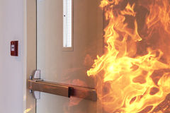 Fire burning in front of the closed door. Royalty Free Stock Photo