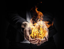 Fire burning in her hands. Young businesswoman holding fire flames in palm Royalty Free Stock Image