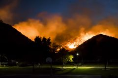 Fire Burning in Hillside above Park During California Wildfire. Fire burning in hills above suburban neighborhood park at night during California Woolsey Fire royalty free stock images