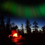 Fire burning at night in a forest. Camping fire burning at night in a forest with northern lights Stock Photography