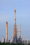 Fire burning over oil refinery chimney against blue sky Stock Images