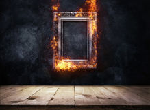 Fire Burning silver Antique picture Frame on dark grunge wall wi. Th Wooden table top, Empty ready for product display or montage Stock Photography