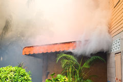 Fire burning and smoke over the house. Stock Photos