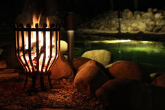 Fire burning at the wellness center. Fire burning beside a pond relaxation at the wellness center with stones Stock Photos