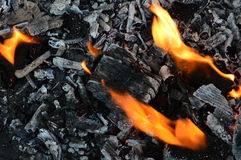 The fire burns. Black embers of a fire and the flames of a fire stock images