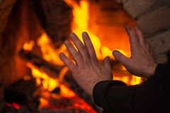 A fire burns in a fireplace, hands in the direction of the fireplace.  stock photo