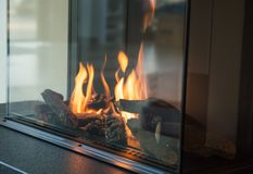 A fire burns in a glass fireplace, radiates heat stock images