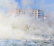 Fire burns grass field brick houses Stock Photos
