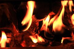 Fire burns in a wood stove charred logs royalty free stock image