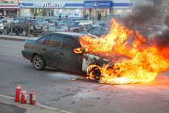 Fire from the car engine hood on city street Royalty Free Stock Photography
