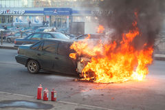 Fire from the car engine hood on city street stock image