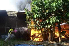 FIRE CAUSE. People are evacuating stuffs as fire rage a home industry in the middle of a dense housings at Sukoharjo, Java, Indonesia. Bad electrical Royalty Free Stock Photography