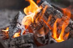 Fire with charcoals. Burning wood. Macro. Live flames with smoke. Wood with flame for barbecue and cooking bbq. Bright color. Royalty Free Stock Photography