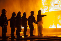 Fire chief directing group of firefighters during  a firefighting exercise Royalty Free Stock Photography