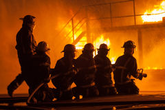Fire chief and firefighters in front of a burning structure during firefighting exercise Royalty Free Stock Photography