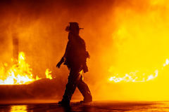 Fire chief walking in front of fire during a firefighting exercise Royalty Free Stock Images