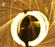Fire circles and sparks. Man creating circles of flames and sparks in a juggling show Royalty Free Stock Photos
