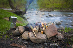 The fire in the clearing near the river. Stock Photos