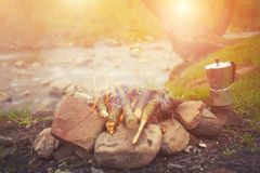 The fire in the clearing near the river. Royalty Free Stock Photo