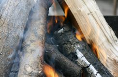 Fire. Closeup of pile of wood burning with flames in the fireplace. Burning tree Bonfire on the grill with smoke. Arson or natural disaster. Bonfire close. Fire royalty free stock photos