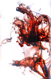 Fire color of paint splashes in water  on white. Stock Photo