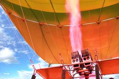 Fire of coral color comes out of a powerful gas torch and fills balloon balloon with hot air royalty free stock photo