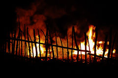Fire in countryside with wooden fence in foreground Stock Photos