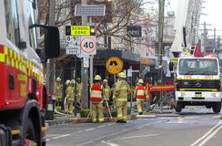 Fire crew and engineers at work at site of explosion. ROZELLE, AUSTRALIA - SEPTEMBER 4, 2014; A team of firemen and engineers at work after a shop explosion in Royalty Free Stock Images