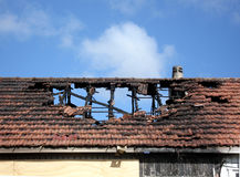 Fire damage on a terracotta tile roof. Burnt char and soot with a clear blue sky