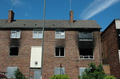 Fire damaged apartments. A fire damaged block of apartment flats.Some of the windows are boarded up and there is a lot of smoke damage Stock Image
