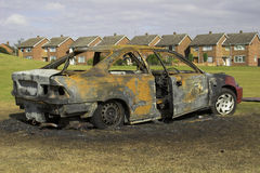 Fire Damaged Car. An urban scene showing a burnt out car on a U.K. housing estate Stock Images