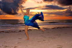 Fire dance. A blonde woman is dancing on beach in front of a fiery sunset with dark clouds Royalty Free Stock Photography