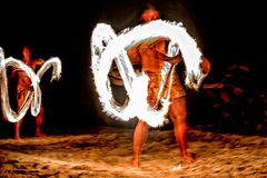Fire dance Cook Islands polynesian dancer with pole of flames royalty free stock image