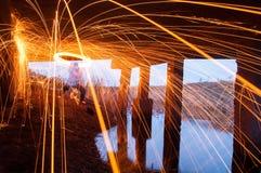 Fire dance show. Steel wool light under the bridge. Stock Photos