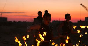Fire dancers against sunset. A young woman poses with her fire hoop against the sunset during her dance performance. stock video footage