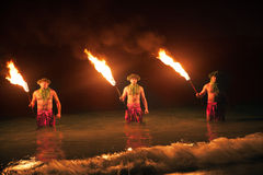 FIre Dancers in the Hawaiian islands at night. Three Maui Men Juggling Fire in Hawaii - Fire Dancers stock photo