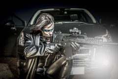 Fire, Dangerous woman dressed in black latex, armed with gun. co Stock Photos