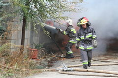 Fire department in action during burning warehouses with plastic products Stock Photography