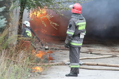 Fire department in action during burning warehouses with plastic products Stock Photos