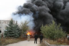 Fire department in action during burning warehouses with plastic products Stock Images