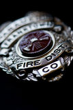 Fire Department Badge. A badge from a fire fighter on a dark background royalty free stock images