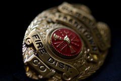 Fire Department Badge. A badge from a fire fighter on a dark background royalty free stock photo