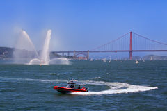 Fire Department Boats and Golden Gate Bridge. In this photo, a San Francisco Fire Department speed boat circles in front of the fireboat Guardian, with the Royalty Free Stock Image